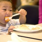 child-holding-a-plastic-fork-in-his-right-hand-with-which-hed-speared-a-piece-of-cantaloupe-725x482