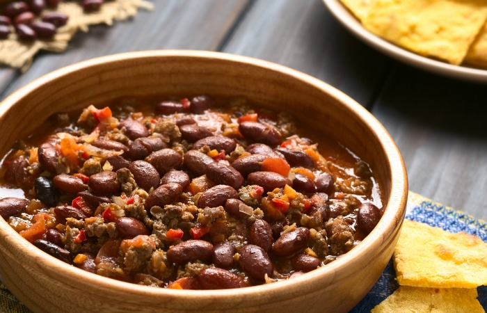 Wooden bowl of chili con carne with homemade tortilla chips in the back, photographed with natural light (Selective Focus, Focus in the middle of the chili)