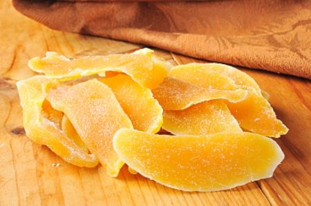 Dried mango or papaya slices on a wooden table