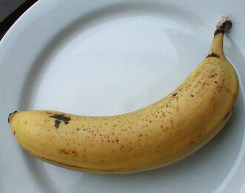 2079 closeup of a banana on a white plate pv