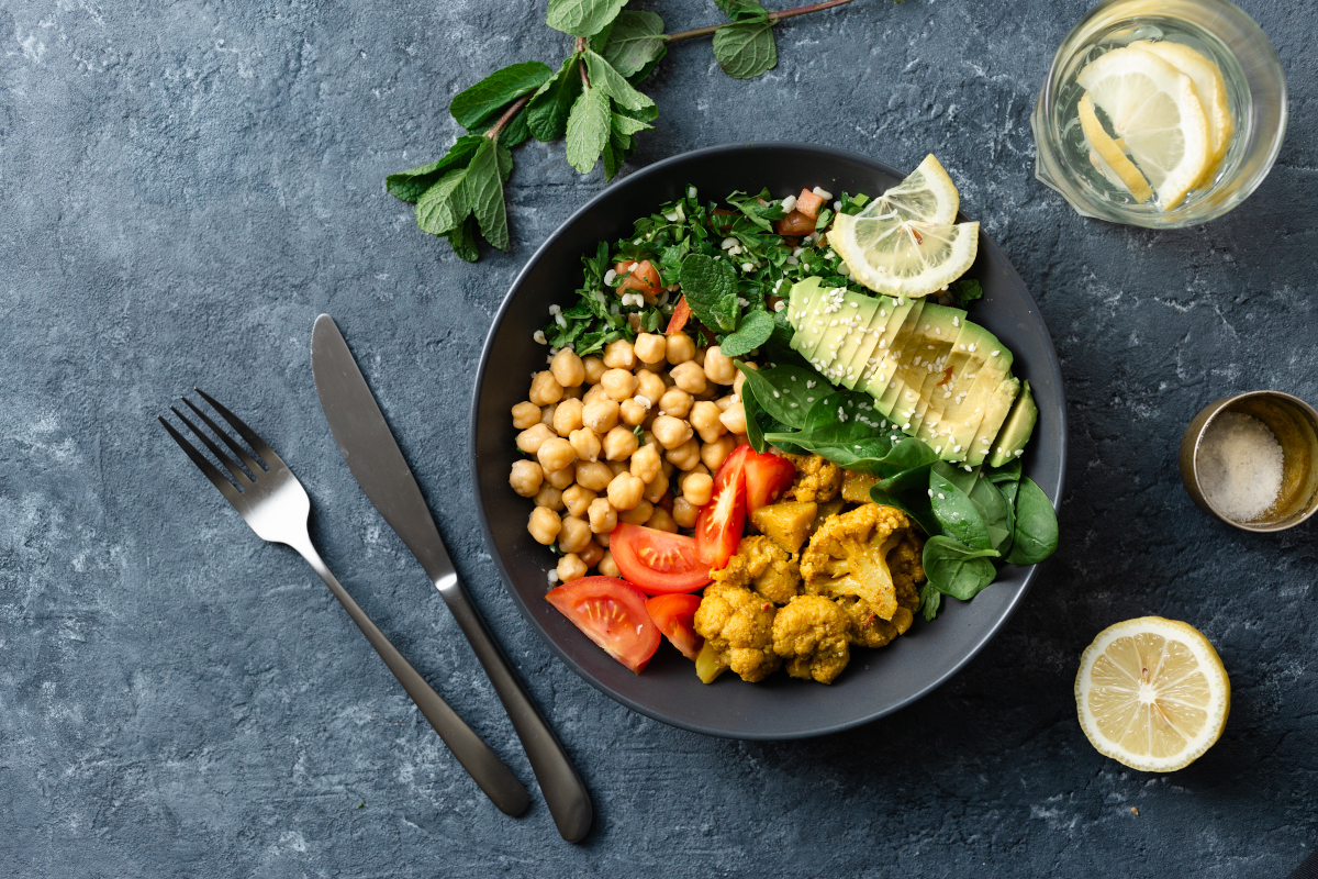 buddha bowl vegetarian healthy balanced food aloo gobi, chickpeas, tomato, avocado, tabule salad spinach