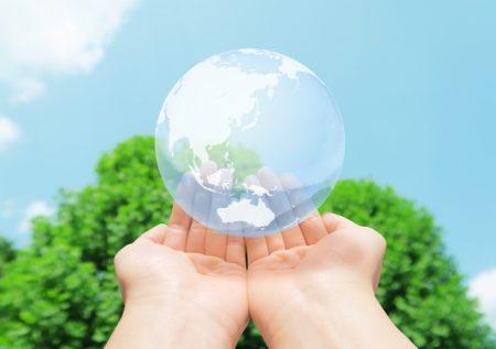地球環境を手の平に乗せる 青空と緑の背景