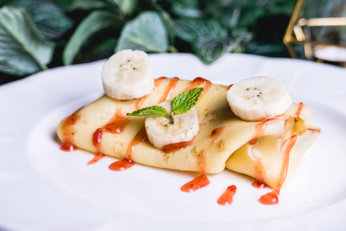 sweet crepe filled with banana set on table.