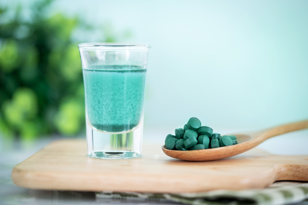 close up vegan blue spirulina smoothie and spirulina pills , a h