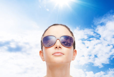 Young female fashion model wearing big sunglasses on sky background