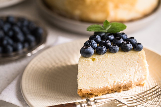 slice of classical new york cheesecake with blueberries on white plate. closeup view. home bakery concept