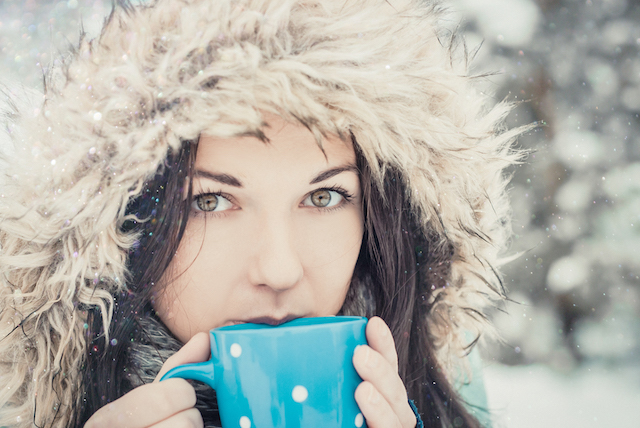woman with big blue mug of hot drink during cold day.