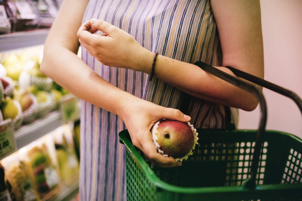 Woman selecting an apple at the supermarket